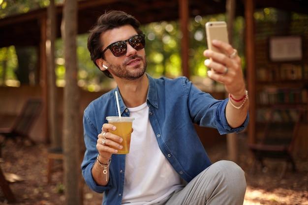 サングラスをかけたハンサムな若いひげを生やした男がジュースを飲みながら公共の庭に座って、スマートフォンで自分撮りをし、カジュアルな服を着て 無料写真