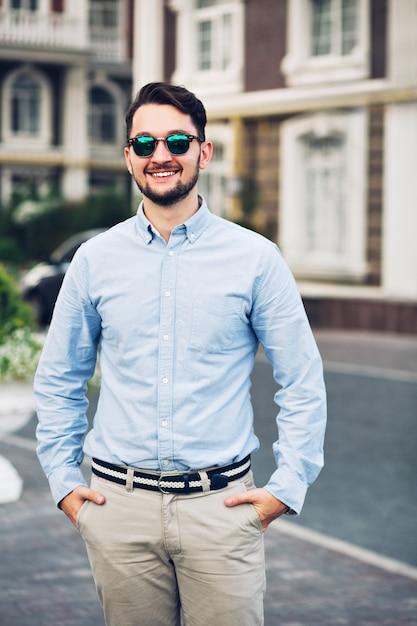 通りを歩いてサングラスでハンサムな青年実業家。彼はポケットに手をつないでいます 無料写真