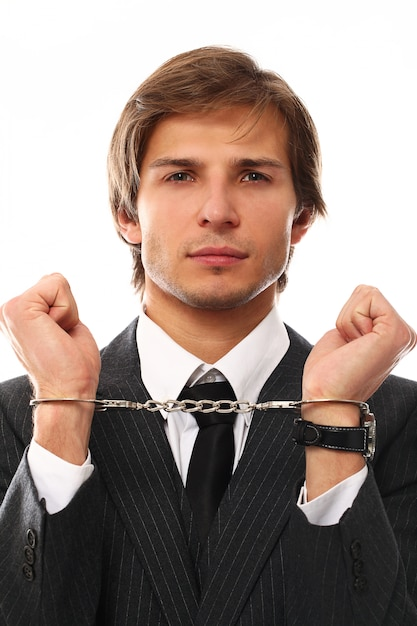 Handsome young businessman portrait with handcuffs Free Photo