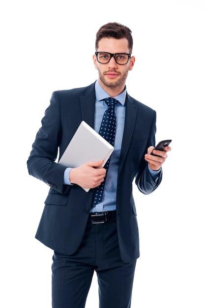 Красивый молодой бизнесмен с цифровым планшетом и мобильным телефоном Бесплатные Фотографии