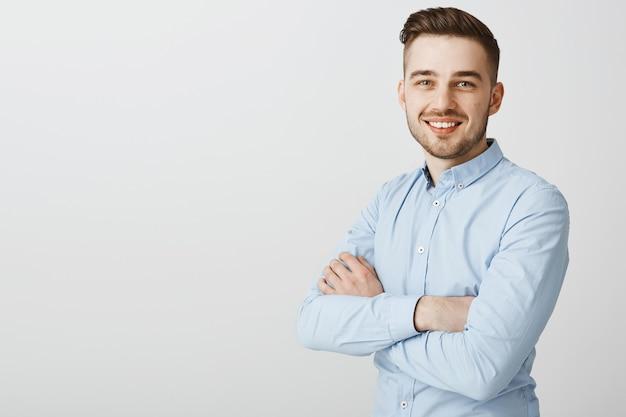 自信を持って笑顔組んだ腕を持つハンサムな青年実業家 無料写真