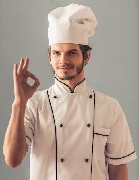 Handsome young cook in uniform is showing ok sign. Premium Photo