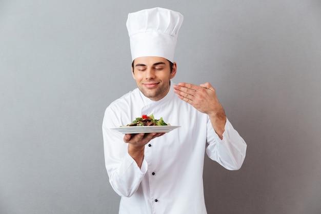 Cuoco bello giovane in insalata di odore uniforme Foto Gratuite