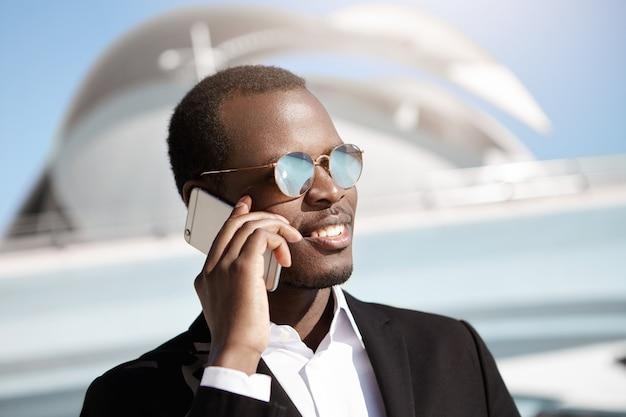 トレンディなミラーレンズシェードと携帯電話を保持している正式なスーツのハンサムな若い浅黒い肌のビジネスマン、彼のパートナーとの会話、ビジネスの問題に関する素晴らしいニュースの共有 無料写真