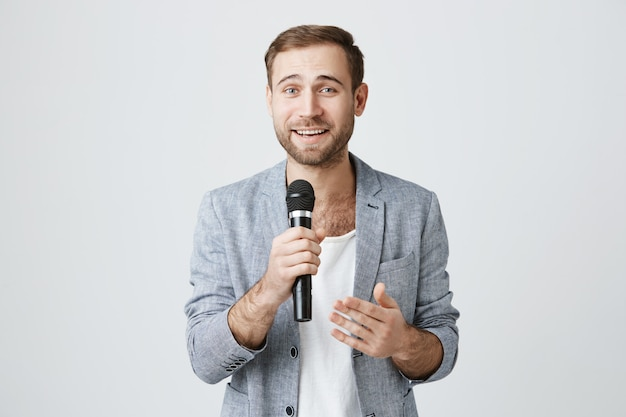 Красивый молодой артист с микрофоном, выступая с речью Бесплатные Фотографии