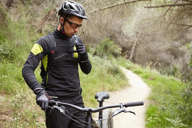 Bel giovane ciclista di montagna europeo in abbigliamento sportivo e abbigliamento protettivo in piedi Foto Gratuite