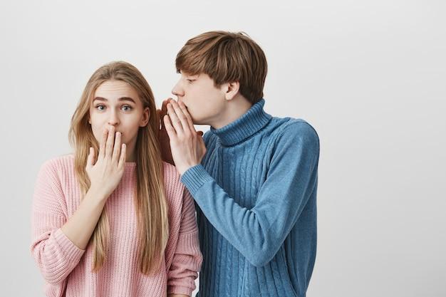 スタイリッシュなブロンドの女の子の耳に何かをささやく青いセーターでハンサムな若い金髪の男子生徒 無料写真
