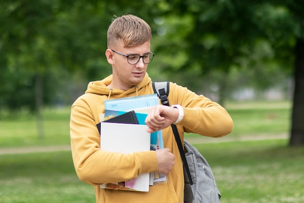 Красивый молодой парень, занятый студент университета или колледжа или ученик с книгами, учебниками и рюкзаком в очках смотрит на свои наручные часы, спешит проверять время, спешит на уроки, сдает экзамены. нет времени. Premium Фотографии