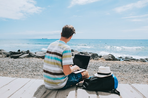 Handsome young guy the photographer working with a laptop on the beach Premium Photo