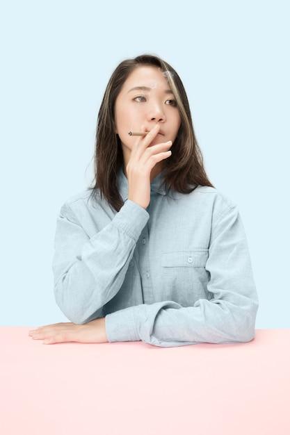 Красивые молодые корейские женщины курят сигару, сидя за столом в студии. Бесплатные Фотографии