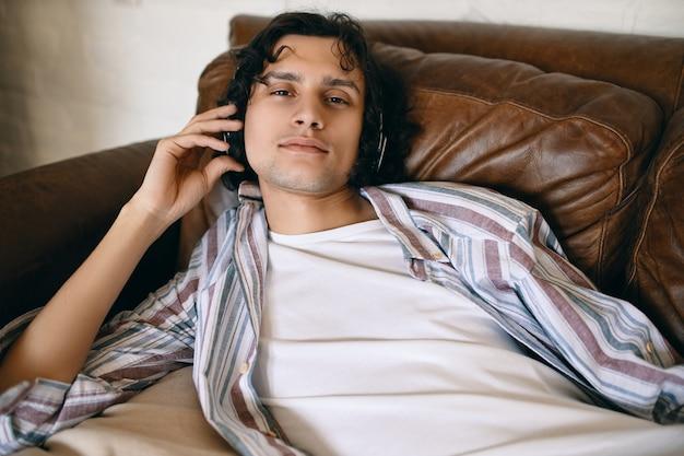 Bel giovane maschio con setole sdraiato sul divano in pelle ascoltando nuovi brani online tramite il servizio di streaming musicale utilizzando cuffie wireless, con un aspetto rilassato. Foto Gratuite
