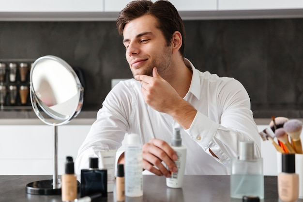 Handsome young man applying makeup and beauty products Free Photo