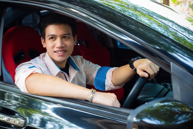 Handsome young man in black car Free Photo
