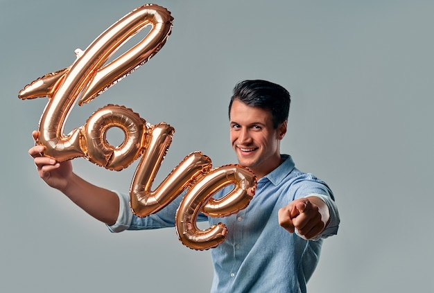 Handsome young man in blue shirt is standing with air balloon labeled love in hand and points a finger at you on grey. Premium Photo