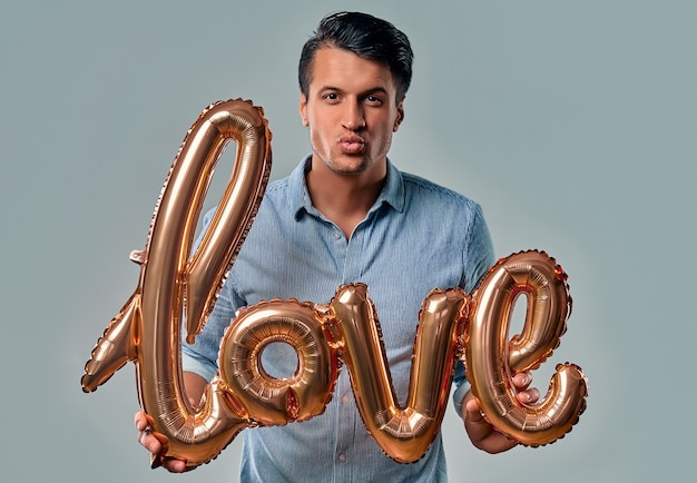 Handsome young man in blue shirt is standing with air balloon labeled love in hands blows a kiss on grey. Premium Photo