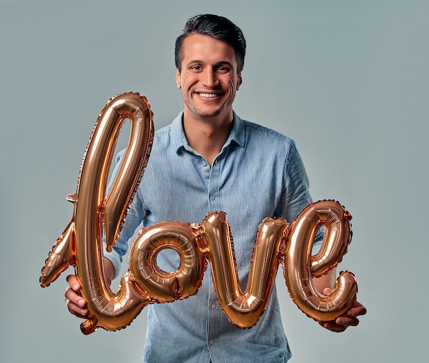 Handsome young man in blue shirt is standing with air balloon labeled love in hands on grey. Premium Photo