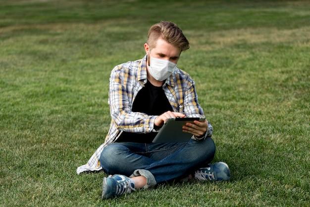 Красивый молодой человек просматривает планшет на открытом воздухе Бесплатные Фотографии