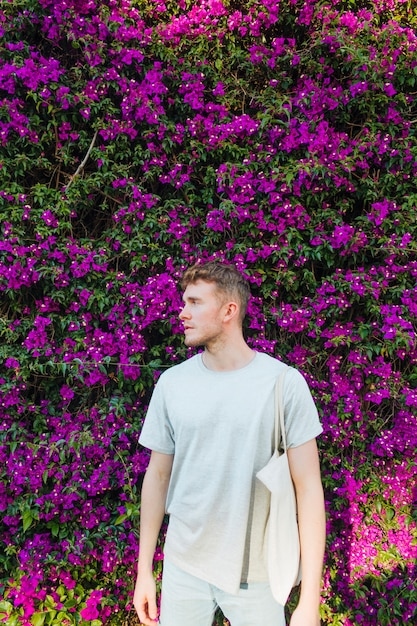 Handsome young man carrying cloth bag standing near pink flower tree Free Photo