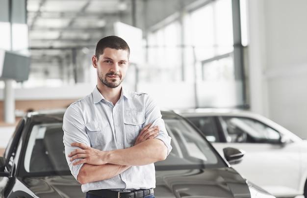 車の近くに立っているカーサロンでハンサムな若い男のコンサルタント。 無料写真