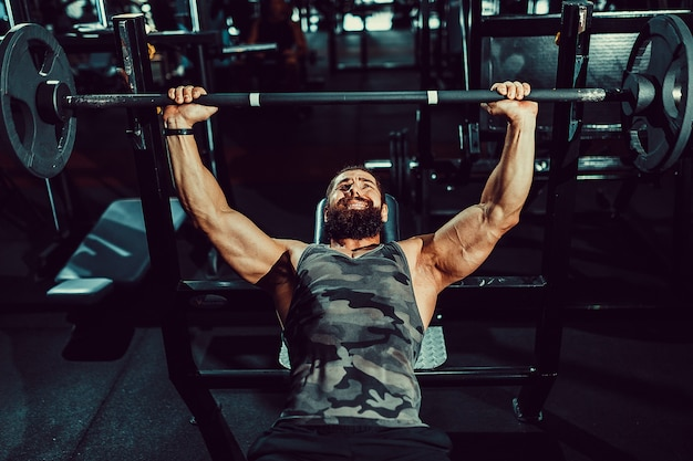 Handsome young man doing bench press workout in gym Premium Photo