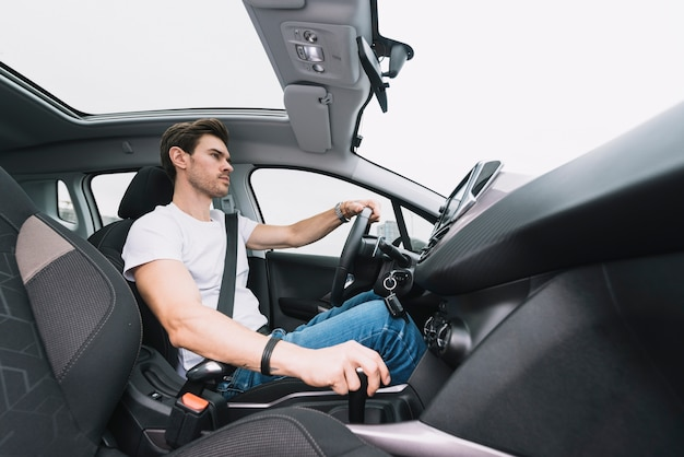Handsome young man driving modern car Free Photo