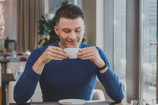 Handsome young man having breakfast at the cafe Premium Photo