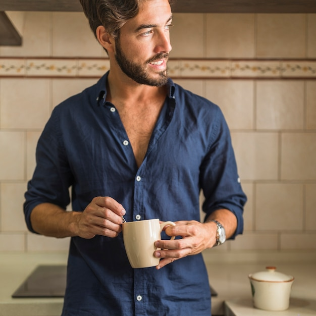 Handsome Young Man Holding Coffee Mug In His Hand Photo
