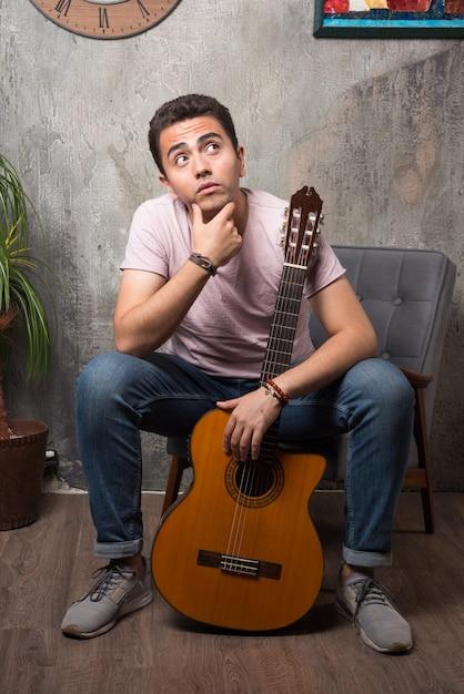 Bel giovane in possesso di chitarra e pensare sulla sedia. Foto Gratuite