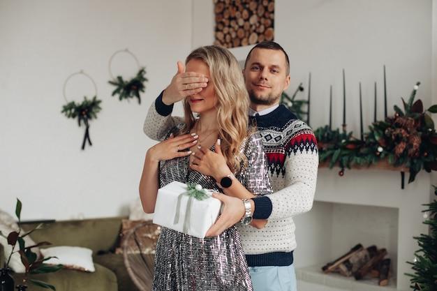 Красивый молодой человек, держащий рукой глаза своей подруги, даря ей специальный рождественский подарок Бесплатные Фотографии