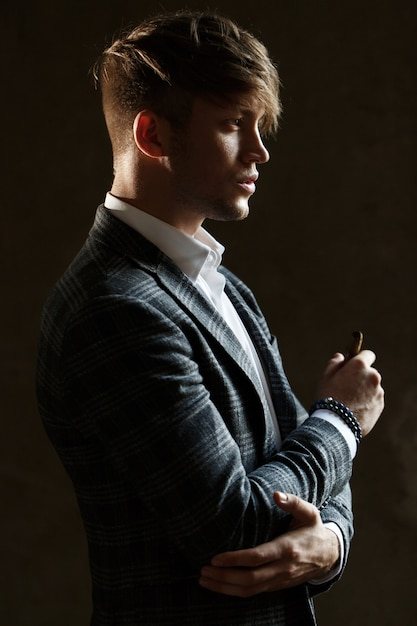 handsome young man in grey suit stands with a cigar photo