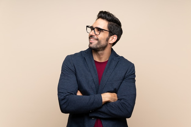 Handsome young man over isolated wall looking up while smiling Premium Photo