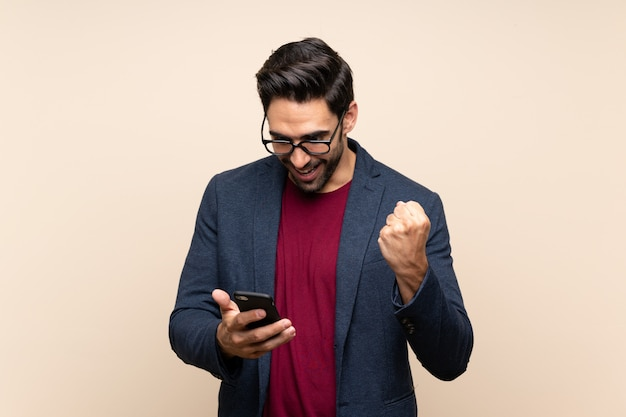 Handsome young man over isolated wall surprised and sending a message Premium Photo