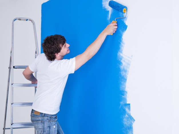 Handsome young man painting the wall in blue Free Photo