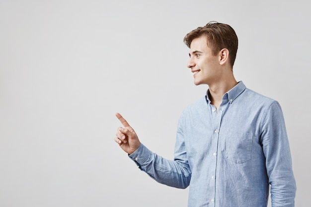 Handsome young man pointing at side with finger Free Photo