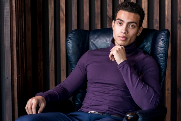 Handsome young man in polo neck t-shirt sitting on armchair looking at camera Free Photo