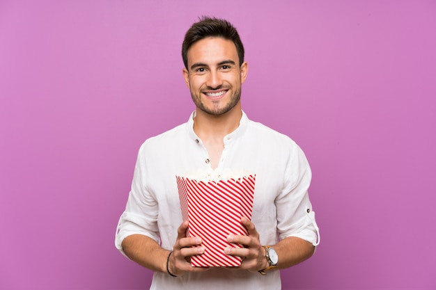 Handsome young man over purple background holding popcorns Premium Photo