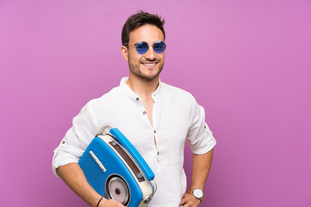 Handsome young man over purple background holding a radio Premium Photo