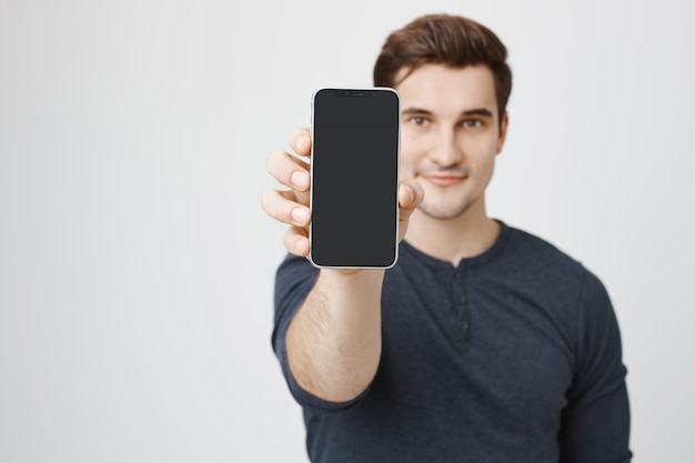 Bel giovane che mostra il display del telefono cellulare Foto Gratuite
