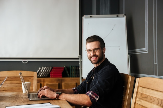 Handsome young man sitting near coffee while working Free Photo