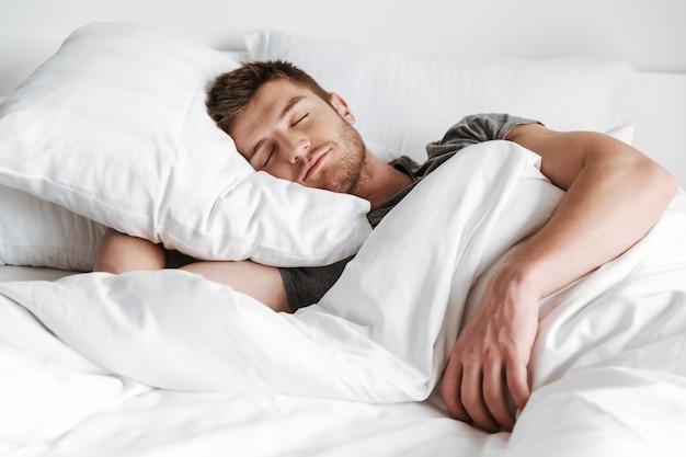 ベッドで寝ているハンサムな若い男 Premium写真