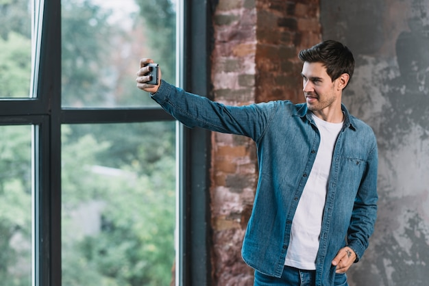 Handsome young man standing near the window taking selfie on mobile phone Free Photo