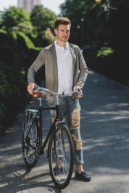 Handsome young man standing with bicycle on street Free Photo