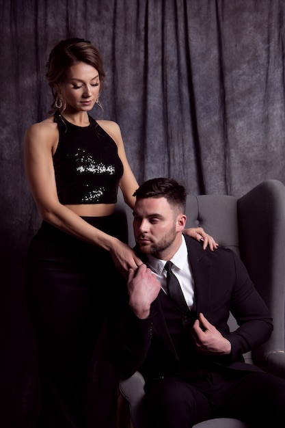A handsome young man in a suit sits in a chair and holds the hand of a beautiful woman in a black evening dress Premium Photo