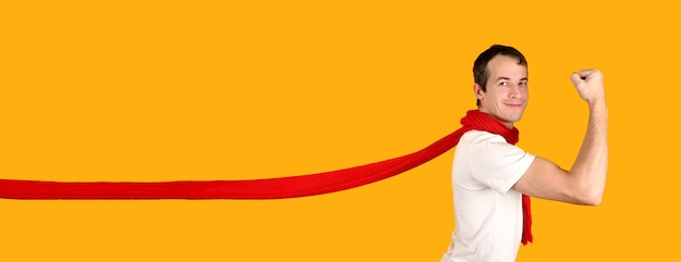 Handsome young man in a superman pose wearing a red flying scarf. studio shot on a yellow background. advertising banner mockup. Premium Photo