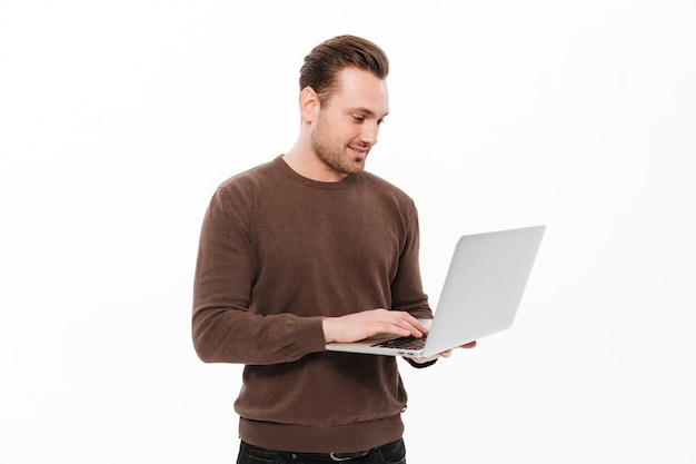 Handsome young man using laptop computer. Free Photo