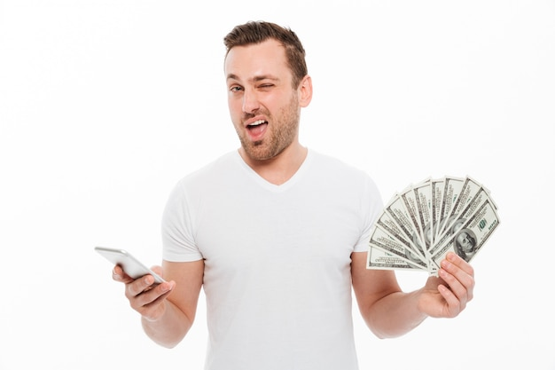 Handsome young man using mobile phone holding money. Free Photo