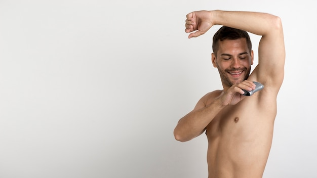 Handsome young man using a roll on deodorant standing against white background Free Photo