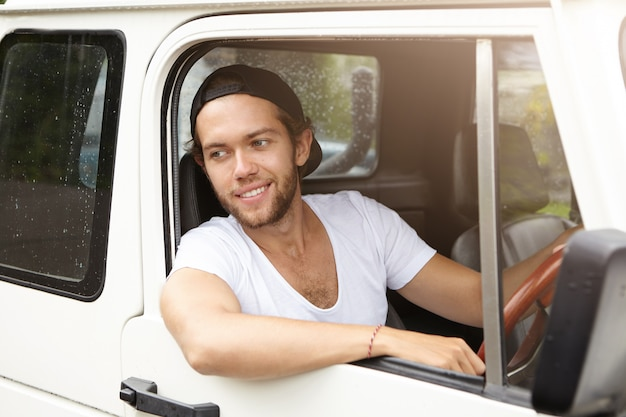 ハンサムな若い男が野球帽をかぶって後方に白いsuv車を運転し、開いた窓から彼の肘を突き出して、笑みを浮かべて 無料写真