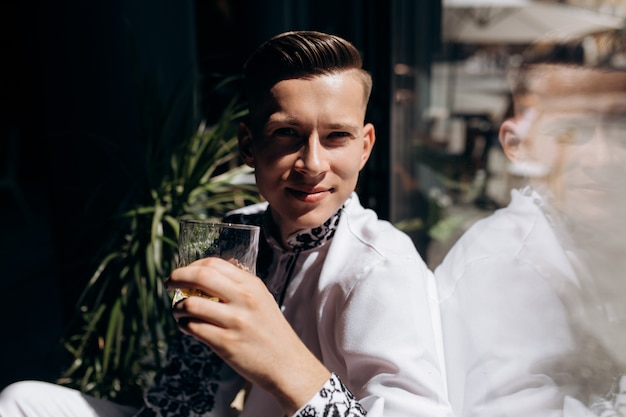 Handsome young man in white suit with embroidery sits on a windowsill before bright window Free Photo