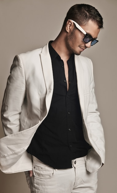 Handsome young man in white suit with fashionable sunglasses Premium Photo